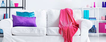 Panorama of white settee with pink blanket and violet and blue pillow in living room interior. Real photo Stock Photo