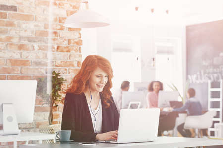 Smiling businesswoman using laptop while working in international company Stock Photo