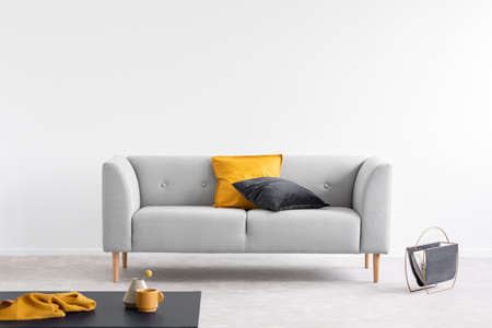 Orange and black pillow on grey couch in grey living room interior with copy space. Real photo Фото со стока