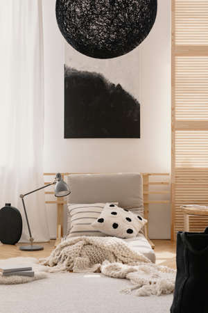 Stylish black chandelier and black and white abstract painting in japanese inspired beige bedroom with pillows, blanket and white carpet, real photo