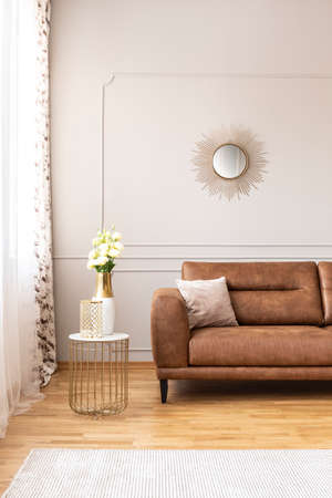 End table with fresh white roses and glass vase sanding by the window with curtains in real photo of bright sitting room interior with round mirror on the wall and brown leather sofa with cushion