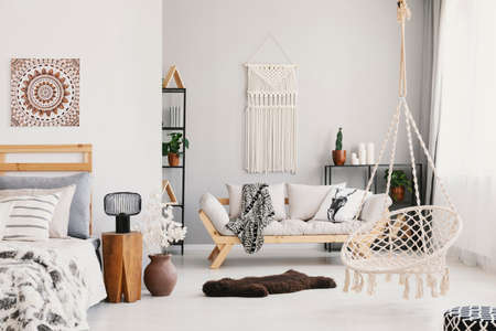 Bright living room interior with macrame on the wall, beige couch with pillow and blanket, hammock chair, fluffy rug and bedside table with lamp standing by the bed in the real photo