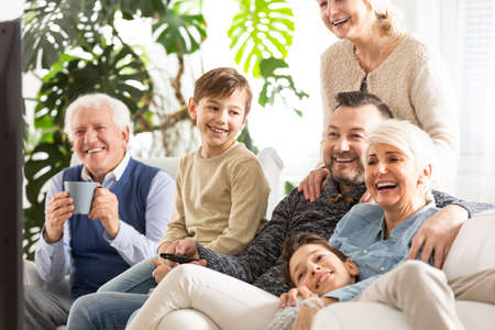 Happy family watching television. Kids sitting next to parents and smiling grandfather
