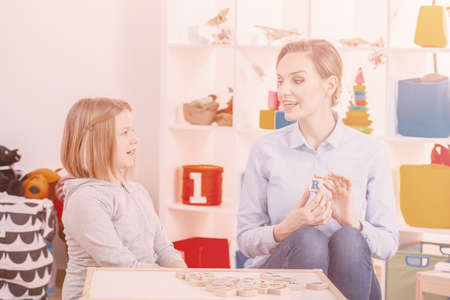 Girl learning alphabet while teacher showing letters on wooden blocks in the school