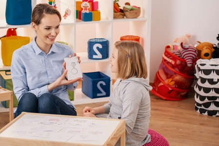 Smiling therapist showing picture of ring during meeting with autistic girl Stock Photo