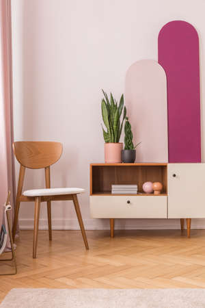 Wooden chair next to cabinet with books and plants in pots, real photo with copy space on the empty white wall Stock Photo