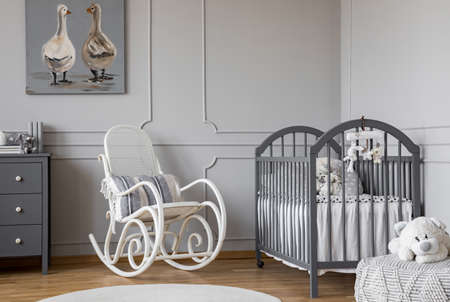 White rocking chair with pillow next to wooden cradle in elegant baby room with ducks poster on the wall
