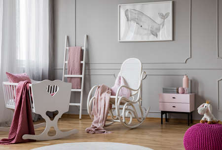 Pastel pink blanket on white rocking chair in spacious baby room interior with cradle, scandinavian ladder and nightstand