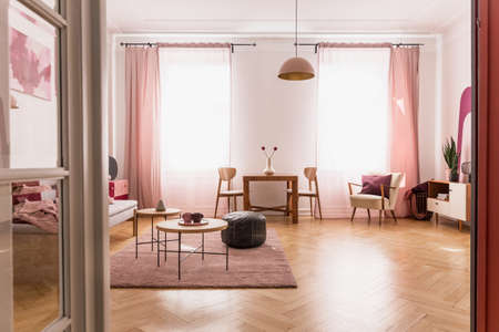 Pale pink living room interior in tenement house, real photo with copy space on the empty white wall and parquet on the floor