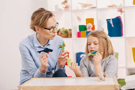 Mother holding toys while playing with daughter at girls room Stock Photo