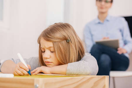 Concentrated girl holding pen while writing exercises during classes