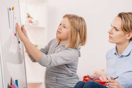 Psychologist analyzing behavior of girl with autism during therapy Stock Photo