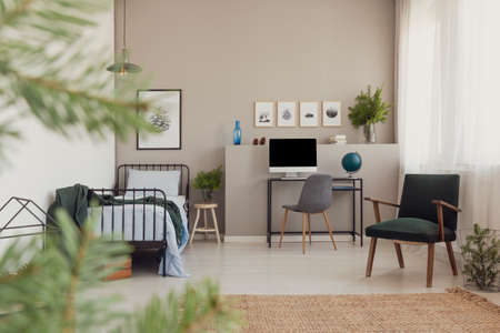 Forest inspiration in trendy teenager bedroom with vintage armchair, desk with computer and branches of spruce in glass vase