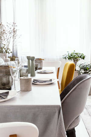 Real photo of table with dinnerware, candle and grey and yellow chair standing in bright dining room interior with window with curtains Stock Photo