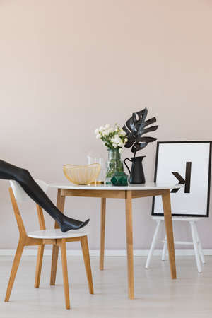 Black mannequin's leg on wooden chair in elegant dining room interior with copy space on the empty wall 写真素材