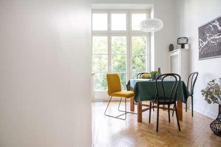 Tafel met donkergroen tafelkleed, tijdschrift, verse citroenen en plant in echte foto van wit eetkamerinterieur met visgraatparket, glazen lamp en balkon. Lege muur met plaats voor je afbeelding Stockfoto