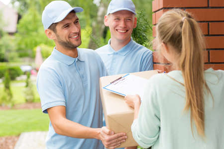 Smiling couriers in blue uniforms giving package to a customer