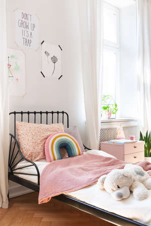 Pink bedding and teddy bear on small kids bed in stylish bedroom of elegant apartment Stockfoto