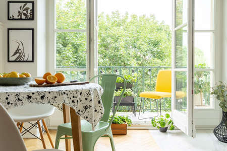 Copper mint chair placed by the table with fresh fruits and lastrico tablecloth in real photo of white room interior with balcony with plants and lights Stock fotó