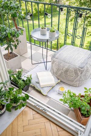 Blick von oben auf den Balkon mit Lichtern, frischen Pflanzen, Tasse mit Tee, offenem Buch und Materialhocker in echtem Foto