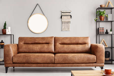 Mockup of round mirror on grey wall in living room interior with brown leather settee. Real photo