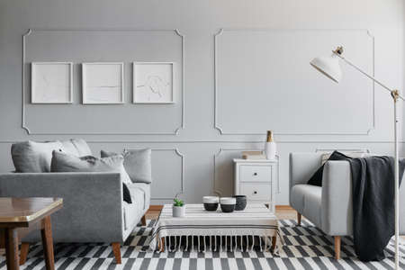 Grey spacious living room with two comfortable sofas and small coffee table covered with striped tablecloth, real photo with mockup on the wall