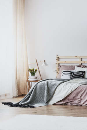 Lamp and plant on table next to wooden bed with grey and pink sheets in bedroom interior. Real photo