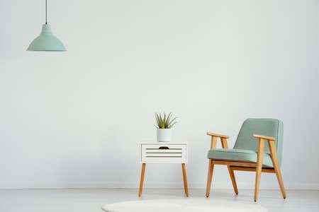 Pflanzen Sie auf dem Schrank neben dem grünen Holzsessel im flachen Innenraum mit Lampe und Kopienraum. Echtes Foto