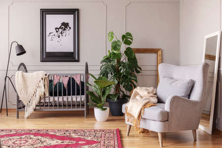 Grey armchair and plants in babys bedroom interior with lamp next to cradle and poster. Real photo
