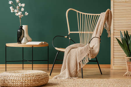 Pouf in front of table with flowers next to armchair with blanket in green loft interior. Real photo Imagens