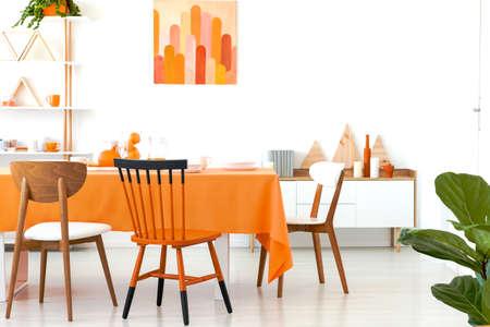 Drie verschillende stoelen geplaatst door de lange eettafel met oranje tafelkleed en serviesgoed. Wit kamerinterieur met rek met decor, eenvoudige poster en kast met boeken