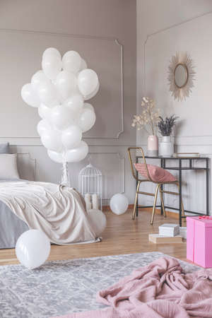 Vertical view of trendy bedroom design with bunch of white balloons, stylish dresser with golden chair and mirror, and pink material on the floor