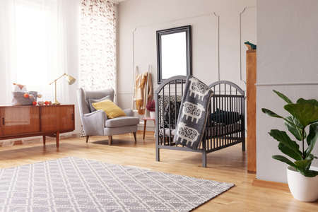 Plant and carpet in bright child's bedroom interior with mockup of poster near cradle. Real photo Archivio Fotografico