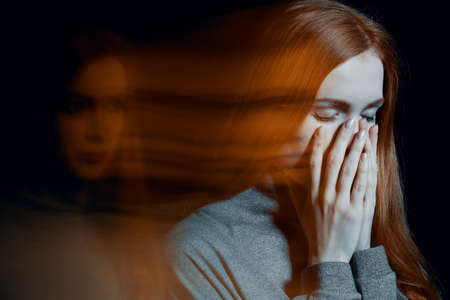 Blurred picture of young beautiful redhead girl with depression covering her mouth Stockfoto