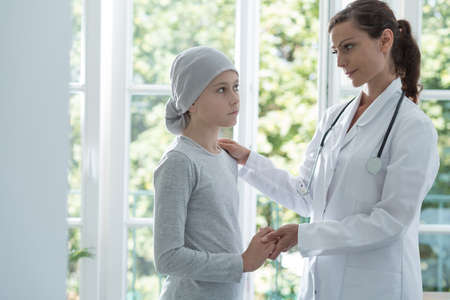 Nurse helping sick kid with cancer wearing headscarf in the hospital Stock Photo