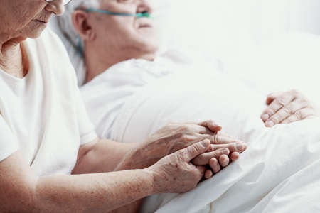 Senior man with lung cancer laying in hospice bed supporting by his elderly wife, photo with copy space