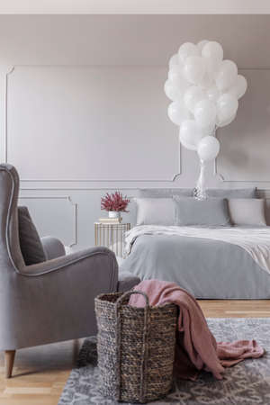 Birthday decoration in grey stylish bedroom with comfortable bed, trendy armchair and basket with pink blanket, real photo with copy space on the empty wall