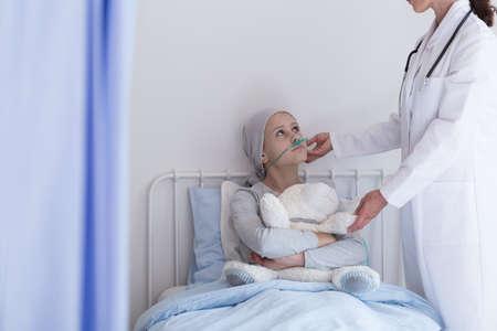 Médecin soutenant un enfant malade atteint de leucémie serrant un ours en peluche pendant le traitement Banque d'images