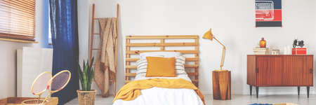 Bed with wooden bedhead, white sheets, ochre cushion and yellow knit blanket in real photo of white teenager room interior with vintage cupboard, ladder with coverlet and window with blue curtain