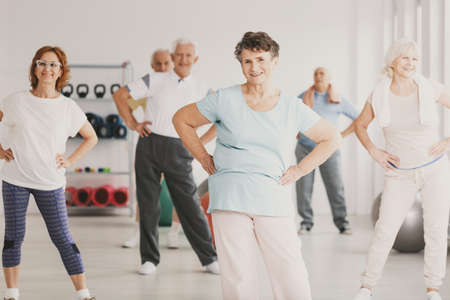 Smiling elderly woman holding hips during gymnastic classes for senior people Stock Photo