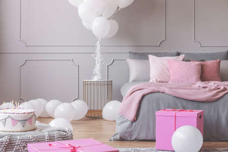 Birthday celebration in bedroom, bunch of white balloons, presents and cake in stylish pink and grey interior, real photo