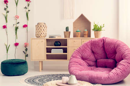 Pink settee in stylish interior with flower board and natural wooden furniture, real photo Banco de Imagens