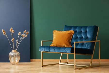 Brown cushion on blue armchair in green living room interior with flowers in gold vase. Real photo 免版税图像