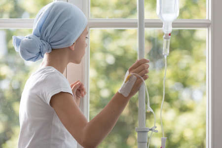 Enfant malade avec goutte à goutte portant un foulard bleu pendant le traitement à l'hôpital Banque d'images