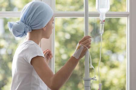 Niño enfermo con goteo con pañuelo azul durante el tratamiento en el hospital Foto de archivo