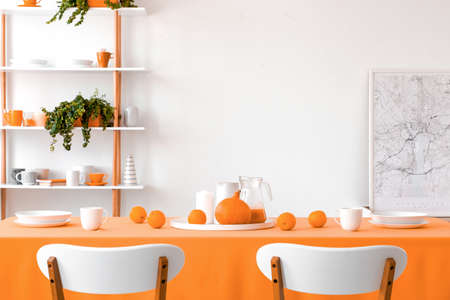 Two chairs placed by the table with mugs, bowls, plates, oranges, pumpkin and homemade juice in white dining room interior with map poster and rack with fresh plants