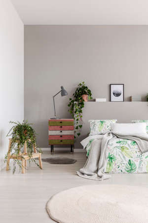 Colorful cupboard with grey lamp in real photo of bright bedroom interior with fresh plants, bed with leafy bedding and blanket and two rugs Banque d'images - 112561063
