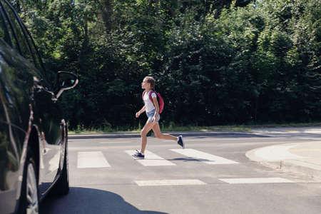 Mädchen mit Rucksack, das neben dem Auto über einen Fußgängerüberweg läuft