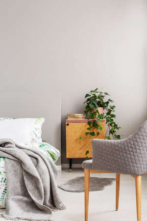 Wooden bedside table with books and fresh plant in real photo of bright bedroom interior with fluffy rug and grey chair 版權商用圖片