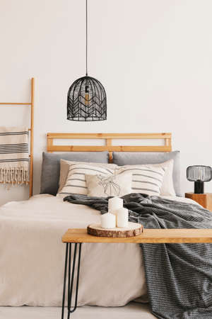 Black trendy chandelier above king size bed with beige duvet, grey blanket and pillows, real photo with copy space on the empty wall